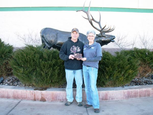 Randy Piearson, President of the Headwaters Chapter, presents Dianna Berry, an assistant manager at Sportsmans Warehouse in Helena, with a major sponsor appreciation plaque.